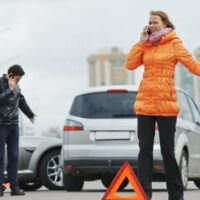 a woman calling the police after a car accident