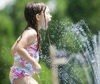 girl playing in sprinkler x